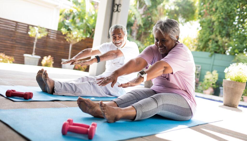 Full length of senior couple doing stretching exercise while sit