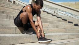 Muscular Dark-skinned Male Athlete In Black Sportswear Holding H